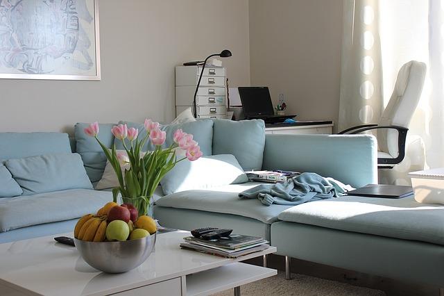 obývací pokoj se světle modrou sedačkou a pracovním koutkem