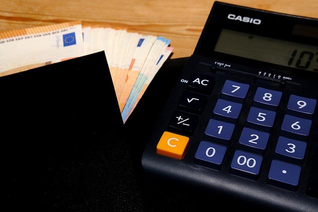 černá kalkulačka a vějíř eurobankovek